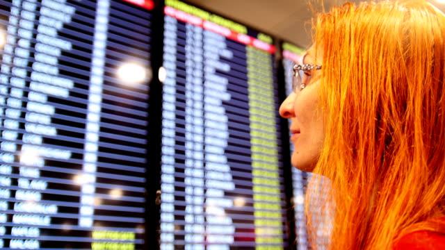 europeiska unga röda hår kvinna tittar på tidtabell avgångs tavla på flygplatsen - blazer bildbanksvideor och videomaterial från bakom kulisserna