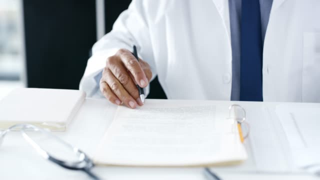 even doctors have their round of admin to do - schedario documento video stock e b–roll