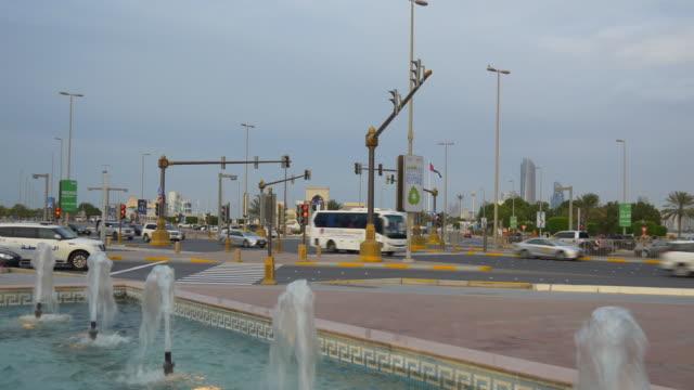 evening abu dhabi marina fountain traffic crossroad street view 4k united arab emirates - uae national day стоковые видео и кадры b-roll