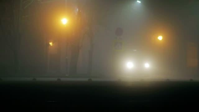 stockvideo's en b-roll-footage met avond stad in dikke mist, ongunstige weersomstandigheden - mist donker auto