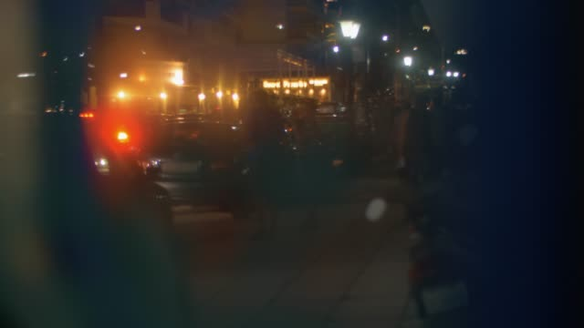 Evening city street with people and cars, view through glass video