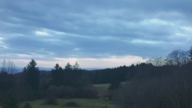 森林に覆われる山の上をレースする夕方の雲 - デッキ点の映像素材/bロール