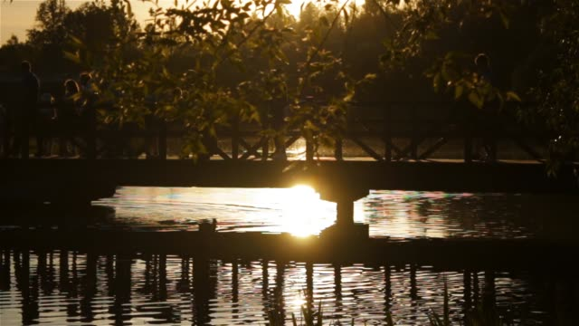 Evening landscape and sunset. People walk along the bridge across the river in the park video