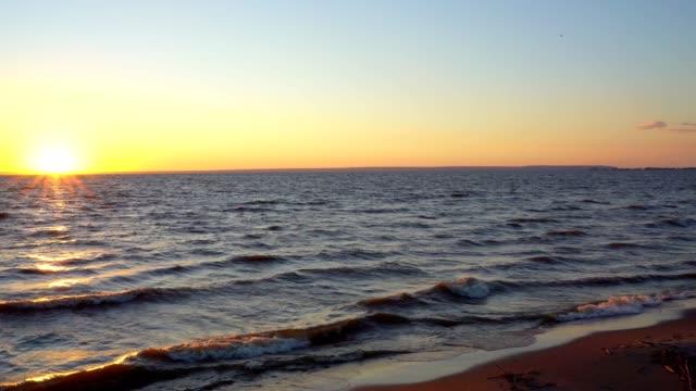 Evening landscape - sky, big lake, sunset, small waves, horizon. Evening landscape - sky, big lake, sunset, small waves, horizon. Quiet summer evening on the lake. rack focus stock videos & royalty-free footage