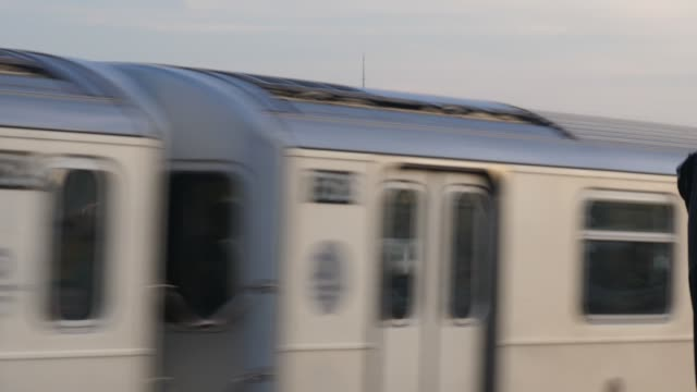 Evening Lower Manhattan Skyline as Subway Car Passes An evening skyline establishing shot of Lower Manhattan as a Queens-bound elevated subway car passes by. underground stock videos & royalty-free footage