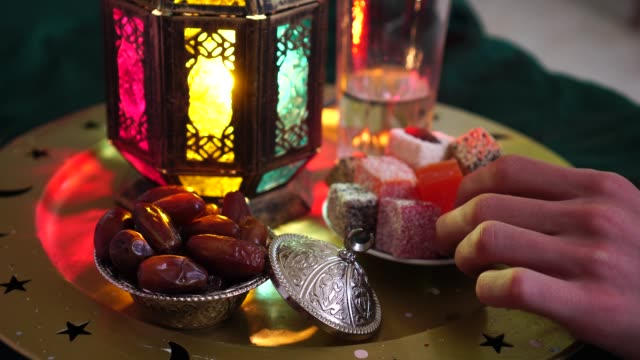 evening meal during the holy muslim month of ramadan. dates, water, sweets and dried fruits. the religion of islam - рамадан стоковые видео и кадры b-roll