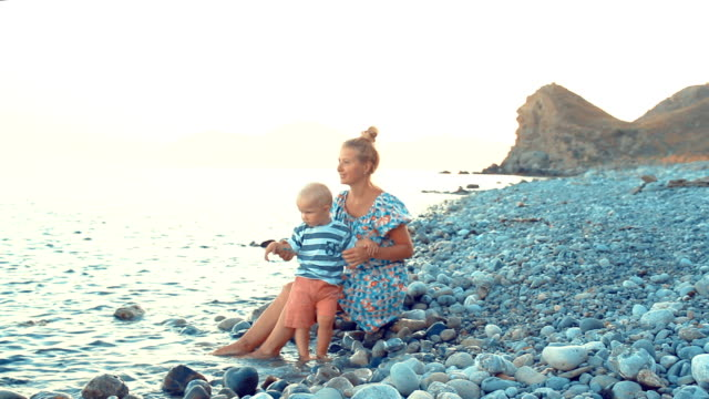 evening, sea beach. the son sits on his mother's lap and eats fruit and berries - pesche bambino video stock e b–roll