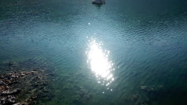 Evening Sunlight Reflecting Off Surface of Emerald Green Lake Reveal Mountains video