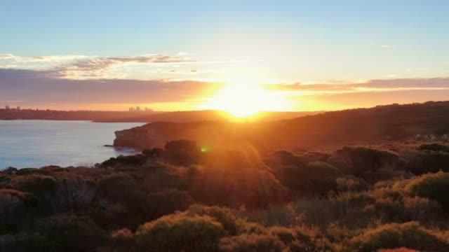 시드니 하버 지역의 저녁 일몰 공중 무인 항공기 영화 패닝 영상, 뉴 사우스 웨일즈, 호주. 노스 헤드, 시드니 하버 국립 공원의 일부, 전경, 배경에 시드니 cbd. - 시드니 뉴사우스웨일스 스톡 비디오 및 b-롤 화면