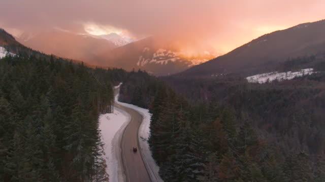 vídeos de stock, filmes e b-roll de antena: sol da noite ilumina o caminho para carro dirigindo pela estrada panorâmica - veículo terrestre
