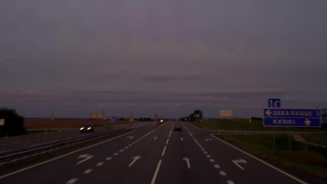 stockvideo's en b-roll-footage met avond track op zonsondergang achtergrond. schieten vanuit de auto vooruit van de auto. filmen van de lading atomobilya. daarnaast rijd ik auto's en vrachtwagens. fullhd - arizona highway signs
