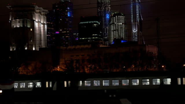 Evening trains in modern metropolis Evening commuter train and railroad engine passing by in metropolis with modern illuminated skyscrapers intercity stock videos & royalty-free footage