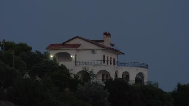 夜の緑の丘の上のコテージのビュー - 別荘点の映像素材/bロール