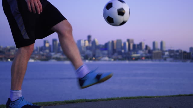 スローモーションサッカージャグリングと夕方ウォーターフロント都市景観 ビデオ