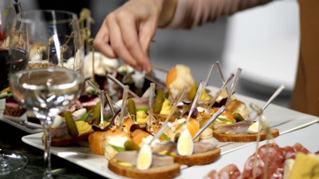 vidéos et rushes de buffet de l'événement. une femme met sur son assiette divers canapes. 4k lente mo - banquet