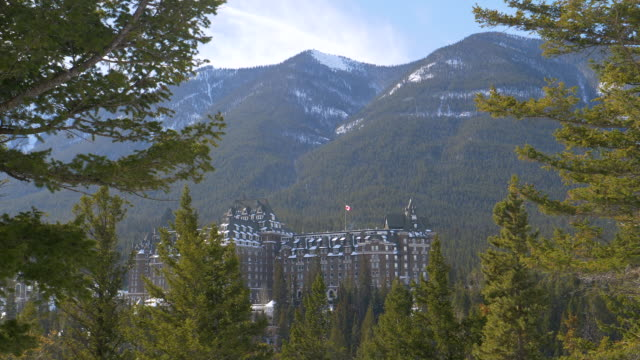 Evergreen forest surrounds the infamous haunted Fairmont Banff Springs Hotel