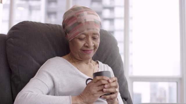 Every day is a gift A black senior woman with cancer is wearing a scarf on her head. She is sitting at home in her living room and is holding a cup of tea. She smiles with gratitude and hope for recovery. cancer patient stock videos & royalty-free footage