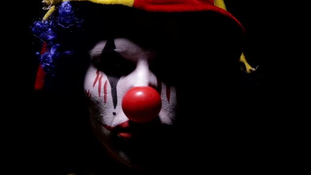 Evil, horror clown man looking into camera video