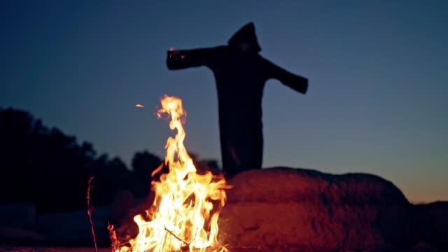 ond häxa i svart kappa med huva nära elden. - bål utomhuseld bildbanksvideor och videomaterial från bakom kulisserna
