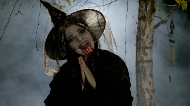 Evil witch zombie with blood on her mouth putting a halloween spell on victim and praying video