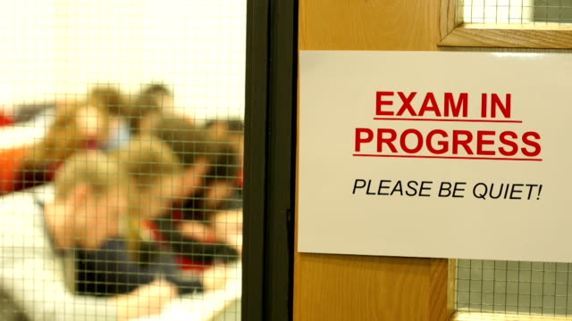 Exam in progress sign with Students behind Stock HD video clip footage of an 'Exam in Progress' sign in focus first with students in Exam room behind educational exam stock videos & royalty-free footage
