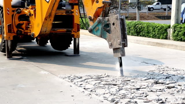 Excavator breaking and drilling the concrete road for repairing video