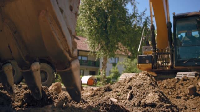 slo mo grävskopa gräva i jorden vid byggarbetsplatsen i solsken - excavator bildbanksvideor och videomaterial från bakom kulisserna