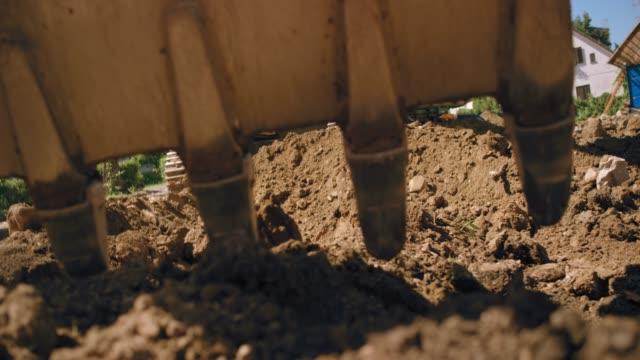 slo mo grävskopa gräva i marken på den soliga byggarbetsplatsen - excavator bildbanksvideor och videomaterial från bakom kulisserna