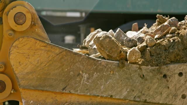 slo mo grävskopan ösregnar fylla med konstruktion skräp i solsken - excavator bildbanksvideor och videomaterial från bakom kulisserna