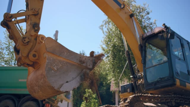 SLO MO excavator bucket picking up the upper layer of the soil at the sunny construction site