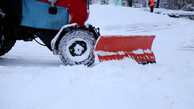 Excavator cleans the streets of large amounts of snow in city. Close-up of a tractor with a large bucket removes snow from the town square. Close-up of iron snowplow pushing a lot of snow away. Snow plow outdoors cleaning street. plow stock videos & royalty-free footage