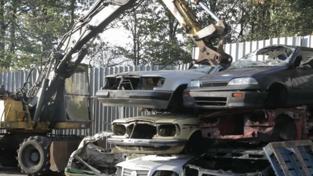 Excavator crashes car in junkyard video