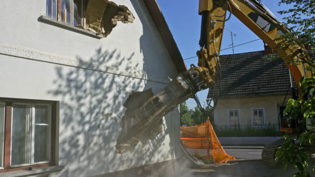 Excavator crumbling the outer wall of an old house being demolished