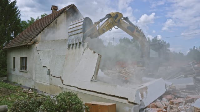 Excavator demolishing an old house in the suburbs by pushing its outer walls Wide handheld shot of an excavator destroying the outer walls of an old building being demolished in the suburbs. Shot in Slovenia. demolishing stock videos & royalty-free footage