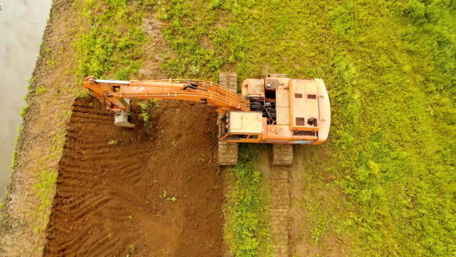 Excavator digging a trench in the field.Aerial video Excavator is digging an irrigation canal. Aerial view:Excavator digging a deep trench.excavator is digging an drainage canal in the agricultural field.4K handful stock videos & royalty-free footage