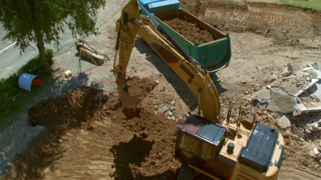 AERIAL Excavator digging into the ground at the construction site and loading the truck with soil Aerial shot of an excavator digging into the ground and loading the truck with soil at the construction site. Shot in Slovenia. construction vehicle stock videos & royalty-free footage