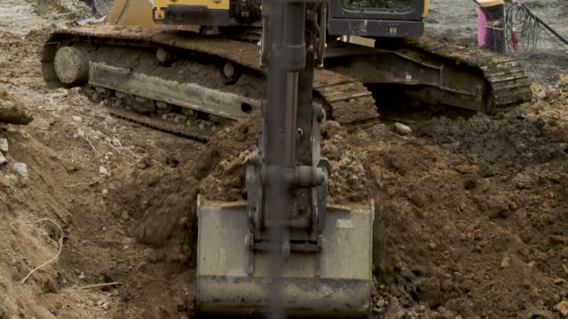 Excavator Digging Out Soil at Construction Site Excavator machine digging out soil at construction site. construction vehicle stock videos & royalty-free footage