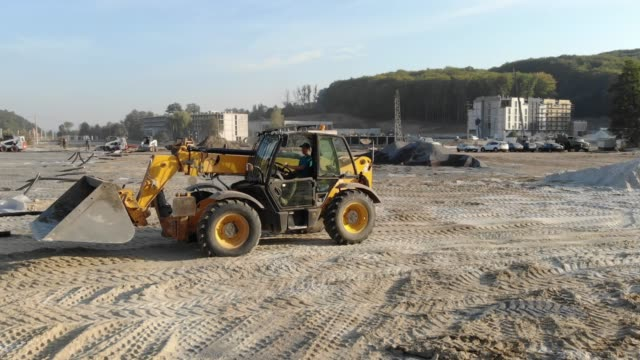 excavator digs sand in the construction of a football field excavator digs sand in the construction of a football field. construction vehicle stock videos & royalty-free footage