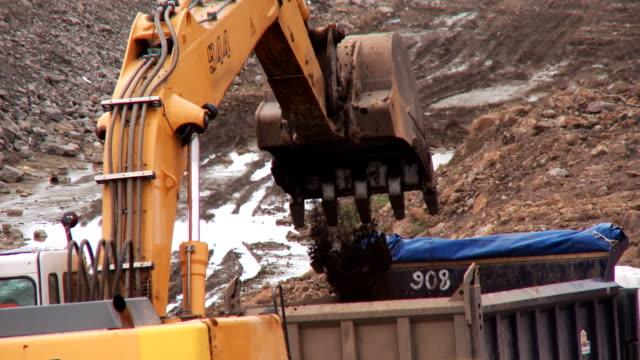 grävmaskin gräver i marken på byggarbetsplatsen och häller den i lastbilen - excavator bildbanksvideor och videomaterial från bakom kulisserna