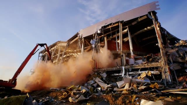 excavator dismantles destroyed hockey stadium in evening