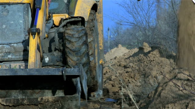 Excavator dripping hole and pours ground from bucket to left side video