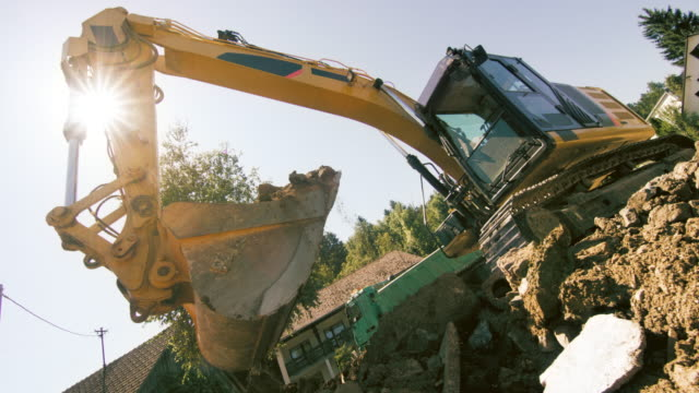 SLO MO Excavator grabbing soil and debris at the construction site in sunshine