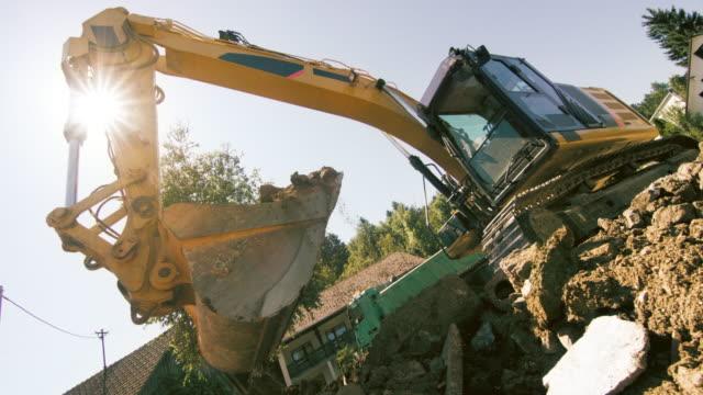 slo mo grävmaskin greppa jord och skräp på byggarbetsplatsen i solsken - excavator bildbanksvideor och videomaterial från bakom kulisserna
