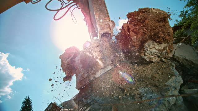 SLO MO Excavator grapples picking up debris in sunshine