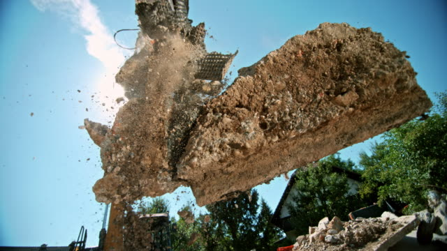 SLO MO Excavator grapples releasing construction debris in sunshine Slow motion wide low angle handheld shot of the grapples on the excavator releasing debris at a building site on a sunny day. Shot in Slovenia. construction machinery stock videos & royalty-free footage