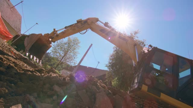 SLO MO Excavator in operation at the sunny construction site Slow motion wide low angle handheld shot of an excavator picking up debris at the sunny construction site. Shot in Slovenia. construction vehicle stock videos & royalty-free footage