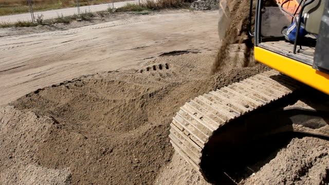 Excavator is preparing pile of sand for loading in truck on building site video