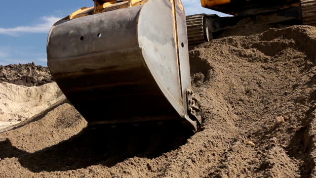 Excavator is preparing pile of sand for loading in truck on building site Yellow excavator is making pile of soil by pulling ground up on heap at construction site, project in progress. civil engineering stock videos & royalty-free footage