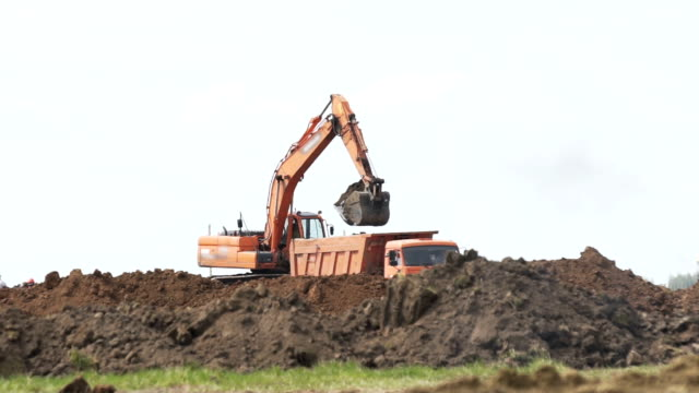 Excavator loading a transportation truck on construction site - video