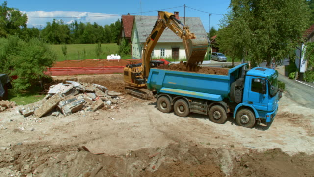 AERIAL Excavator loading a truck with soil at the construction site and spreading it in the trailer Aerial shot of a blue truck at the construction site being loaded with soil by an excavator. Shot in Slovenia. dump truck stock videos & royalty-free footage